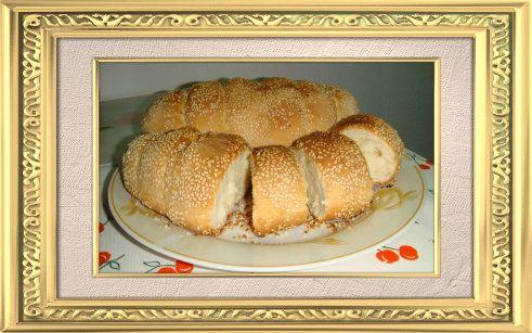 Kıbrıs Köy Çöreği Köy ekmeğinin hamuru gibi hazırlayın. yalnız daha kolay şekil verebilmek için hamurun, ekmek hamurundan biraz daha kıvamlı olması gerekir. Hamurdan bir parça alın ve masanın üzerine, susam ile çörek otu karışımını koyun.