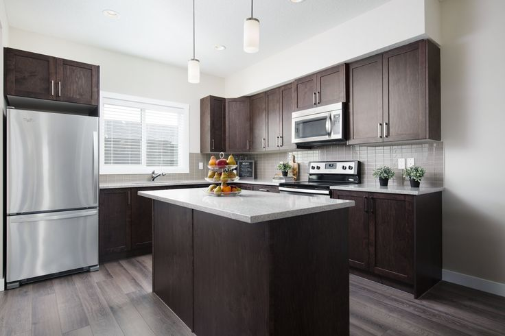 The L-shaped kitchen has a large central island, stainless steel appliances, dark cabinets and light counters creating an eye-catching contrast #kitchen