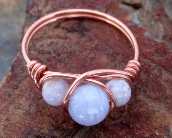 This is a solid Copper wire wrap ring which has been fashioned with two 4mm and one 6 mm Blue Lace Agate stones.    Blue lace agate is a