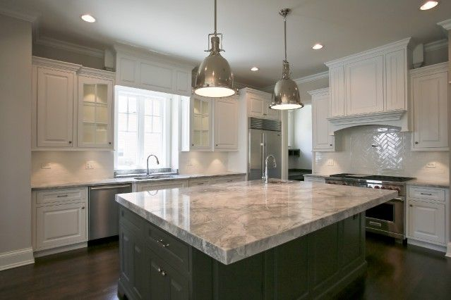 Gorgeous kitchen with white perimeter cabinets accented with nickel hardware alongside gray and ...