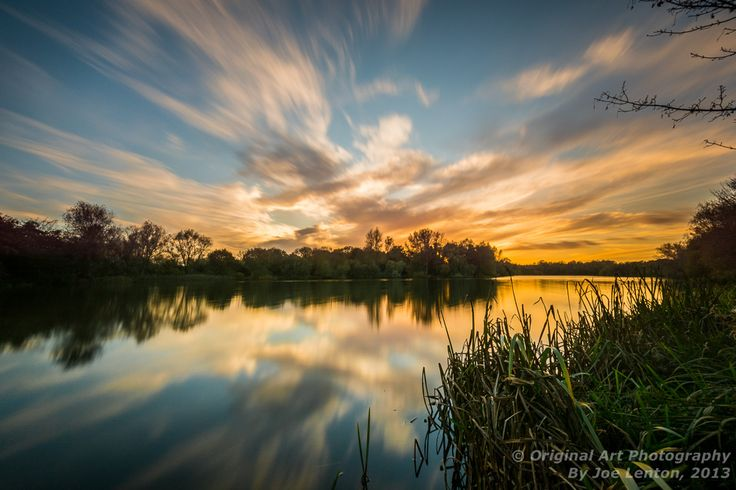 This sunset reflection is a long exposure (30 seconds), smoothing out the water and giving the impression of movement in the clouds. It was taken at the UEA broad, Norwich, Norfolk, UK on a November evening in 2013.