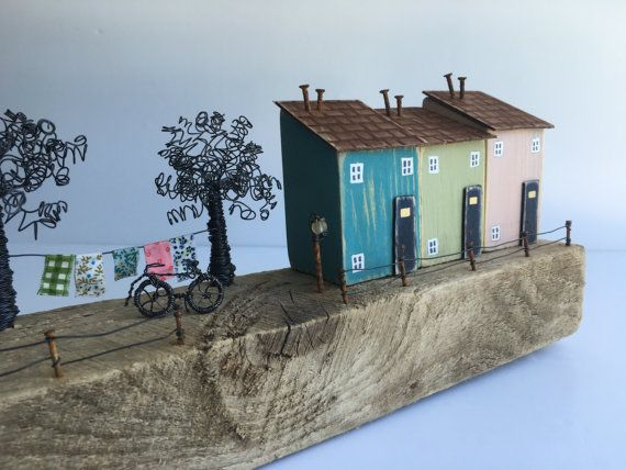 A gorgeous long piece of driftwood forms the base for this piece which has 5 larger pretty hand painted houses, wire trees, washing line and cute hand made wire bike to complete a lovely street scene. The houses have been hand painted using branded chalk paint and given distressed navy doors. The washing on the line co-ordinates with the houses and the street lamps light the way home! The hand twisted wire trees add another texture and dimension The dimensions of this make it perfect for a…
