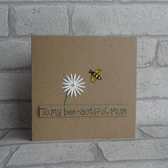 Mothers Day card with a bee and flower for Mum / Mom.  This handmade bee and flower card has a flower (daisy), with a bee approaching it flying in the air. The bee has gems for wings and the the flower colour can be chosen from the drop-down menu. The sentiment on this Mothering Sunday card is added with 3D foam and reads: To my bee-autiful Mum. You can choose other messages or your own message from the drop-down menu.  This bee card would also make a great birthday card for Mum / M...
