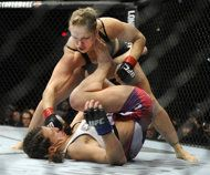 Ronda Rousey of Venice, Calif., punches Miesha Tate of Yakima, Wash., during the UFC 168 mixed martial arts women's bantamweight title fight...