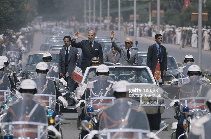 The Official Visit Of Valery Giscard D'estaing In Morocco. Le lendemai matin de son arrivée, déplacement à Fez: debout dans une voiture blanche, escortée par des motards en tenue à l'avant et sur les côtés, GISCARD et le roi HASSAN II saluent la foule massée sur les trottoirs de la ville. A l'arrière, une file de voitures officielles suit le cortège. La température de l'accueil a encore monté. Et les gardes du corps sont aussi souriants que GISCARD.