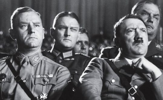 A visibly disgusted Hitler and fellow government officials view a science documentary commissioned by the NSDAP which covered racial as well as genetic studies, much of which as an attempt to explain (or reinforce) reasons to why certain ethnic/racial groups are superior to others societally. Such films made by German researchers and film crews displayed the most troubling depictions of racial groups, notably those of the Jews and Africans, covering the worst aspects of each.