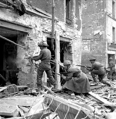 Canadian soldiers fire into a battered house. 10 July 1944, Caen, France.