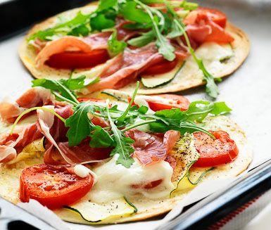 Ett superenkelt recept på tjusiga tortillapizzor med mozzarella och lufttorkad skinka. Du gör pizzorna av bland annat zucchini, mozzarella, tortillabröd, skinka och ruccola. Passar bra att servera som förrätt.