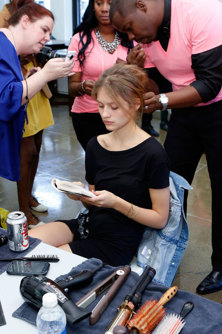 This model read a book while being primped for the Carmen Marc Valvo Spring 2013 show at Mercedes-Benz Fashion Week.