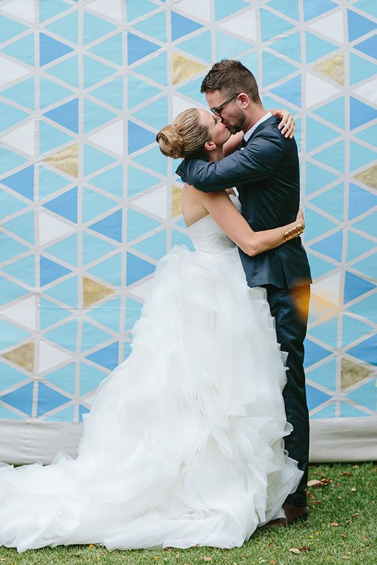 Kate and Anthony's Quirky Garden Wedding. Colorful metallic geometric painted backdrop.