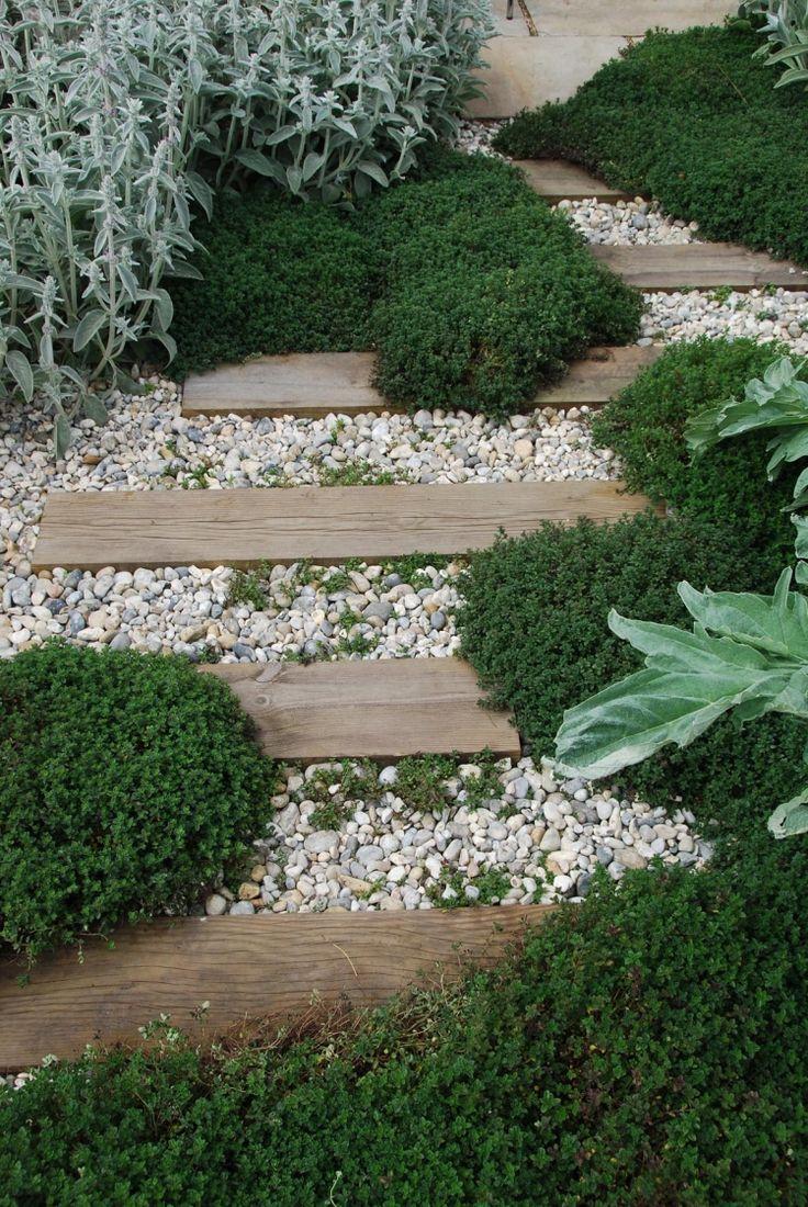pas japonais en planches de bois et gravier concassé et plantes couvre-sol