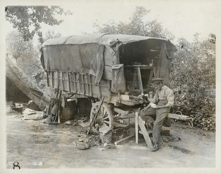 A covered wagon serves as a Canadian Field Post Office. The seated soldier was likely assigned to sorting the mail. Canadian mail went through London where it was bagged and delivered to units by ration train. It took a minimum of about three weeks for Canadian mail to arrive at the front.