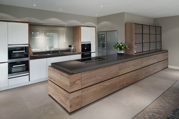 Een moderne keuken komt tot leven door de combinatie van strak witte fronten en levendig olijfhout. Verborgen blikvanger is de geïntegreerde afzuigkap
