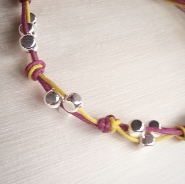 Braccialetto con cordino colorato annodato con perline di argentate : Braccialetti di gicabijoux