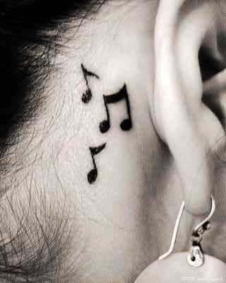 pequeño tatuaje de notas musicales detras de la oreja