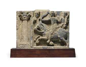 A gray schist relief with the archery contest  Gandhara, 2nd/3rd century  Carved with Siddhartha drawing a bow on his steed Kanthaka in full gallop, flanked by two attendant figures, separated from a large column at left 12 7/8 in. (32.7 cm.) wide