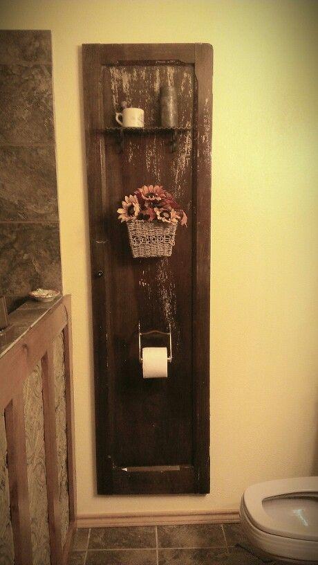 Rustic bathroom decor-old pantry door used in my bathroom,horse bit repurposed as toilet paper holder. Husband did a great job !!