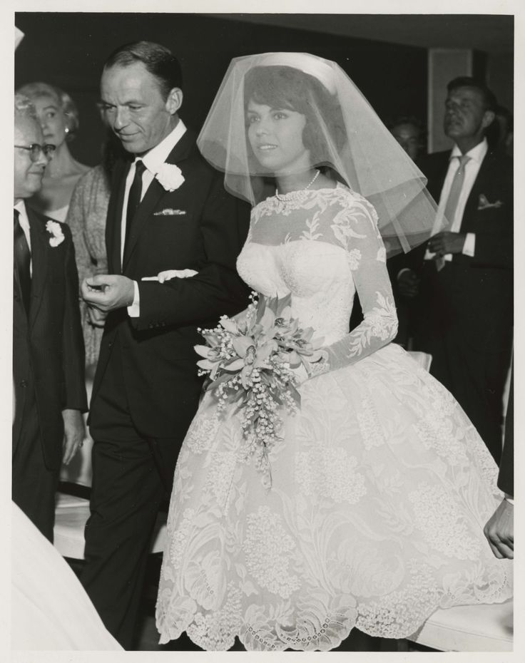 """Photograph of Frank Sinatra walking his daughter, Nancy Sinatra, down the aisle at the Sands Hotel in Las Vegas, September 11, 1960. Photograph is part of the UNLV Libraries """"Photo"""" digital collection."""
