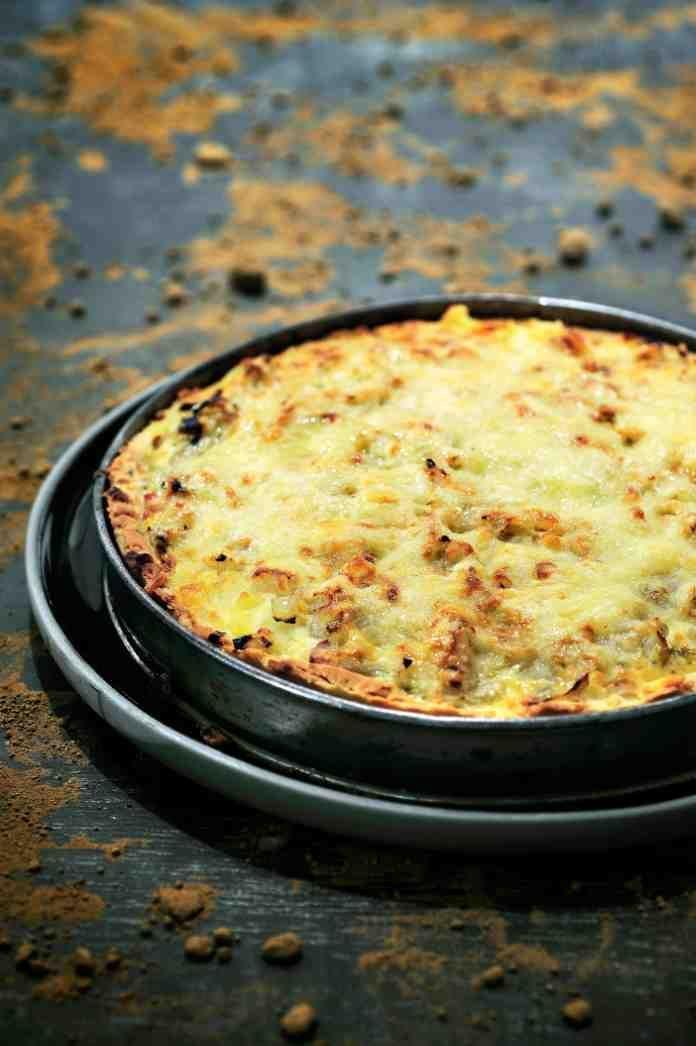 Bereiden: Stoof het witloof aan in de boter en laat goed uitlekken zodat al het vocht zo veel mogelijk verdwijnt. Snijd de aardappel in blokjes en doe hetzelfde met het spek. Stoof aan. Maak het deeg: wrijf de bloem en de boter met de handen door elkaar, tot er een kruimelig mengsel ontstaat. Voeg de andere ingrediënten toe, kneed kort en krachtig. Laat 15 minuten rusten. Neem een taartvorm, doe het deeg er in en dek af met bakpapier. Doe er wat kiezelsteentjes op zodat het deeg niet omh...