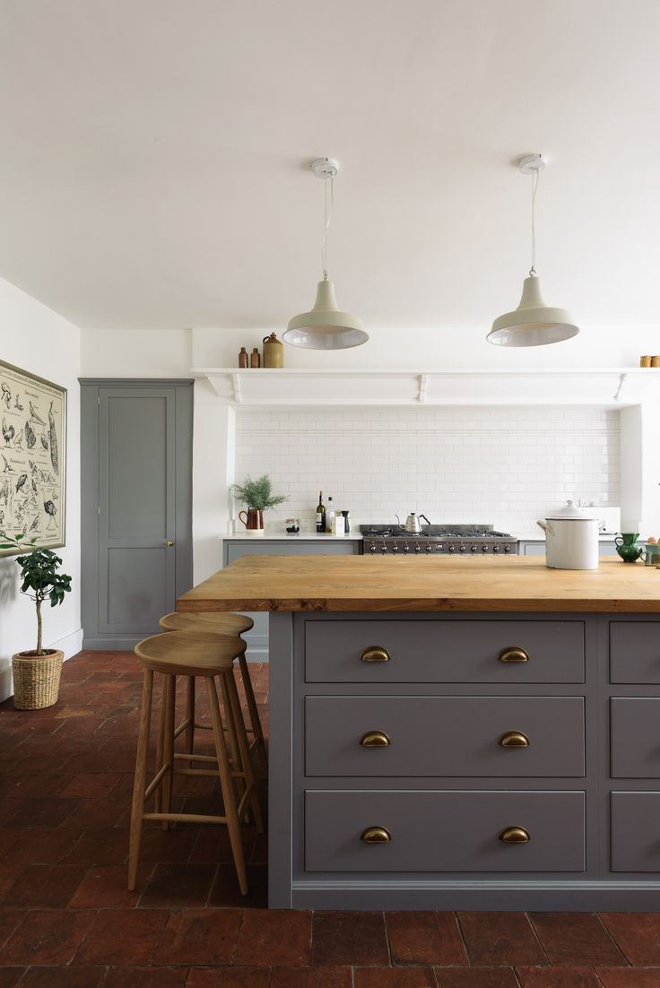 Deep pan drawers provide plenty of storage in this kitchen island, finished with brass hardware and rustic oak worktop