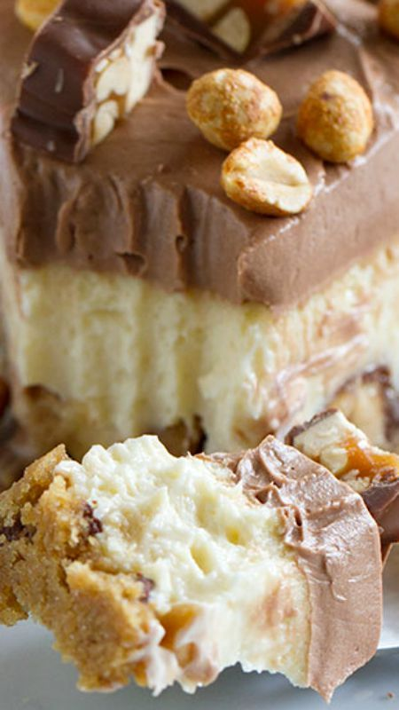 Snickers Cheesecake ~ a graham cracker crust, chunks of Snickers candy bars, a creamy cheesecake layer, then a smooth, chocolate cream cheese frosting. Topped with more Snickers and peanuts