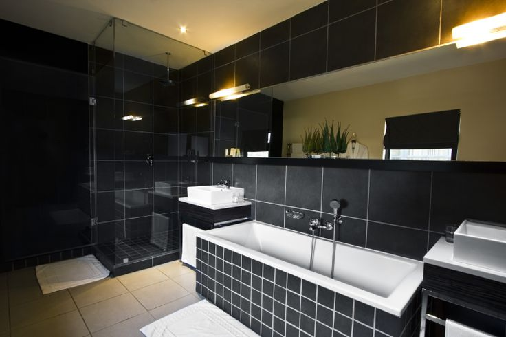 Luxury Bathroom - Black: These suites have large floor to ceiling windows overlooking the rolling landscape of the Klipriviersberg; they are located in the bush area of Thaba Ya Batswana ensuring quiet privacy. Each air-conditioned suite is equipped with large screen LCD television, and iPod docking station