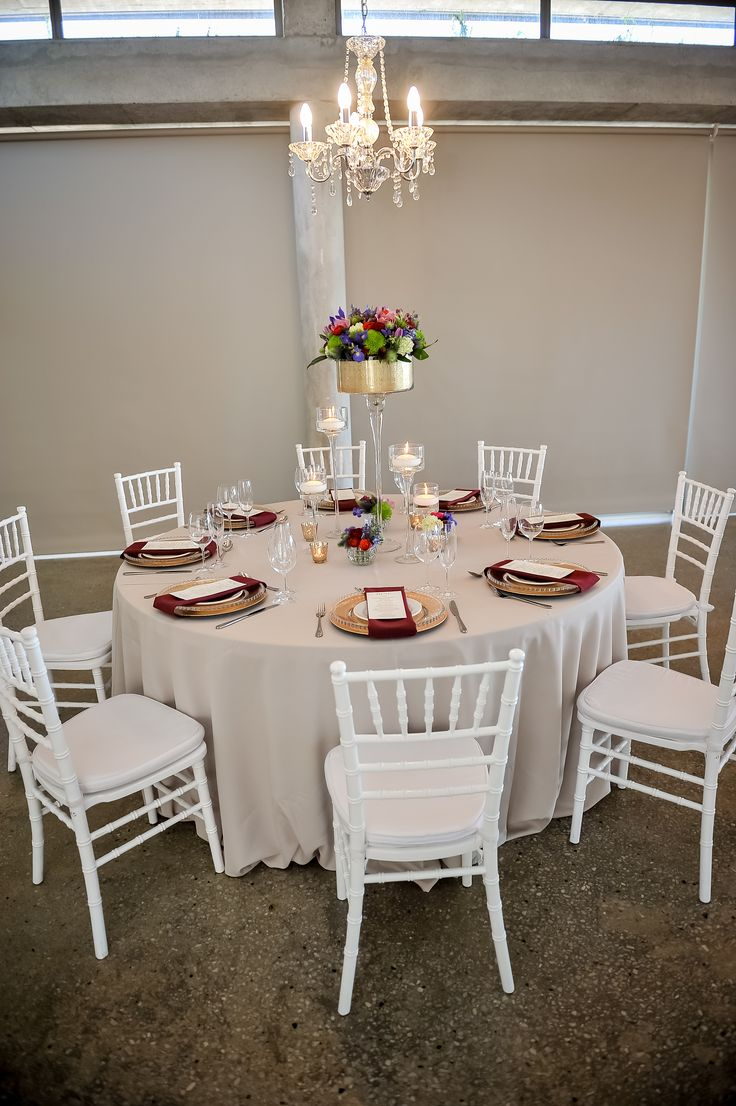 Stone colour table cloth, white Tiffany chairs with gold decor detail and colourful flotal. Chandelier on top.
