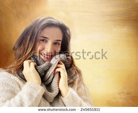 smiling girl with winter clothes and wool scarf against golden abstract background - stock photo