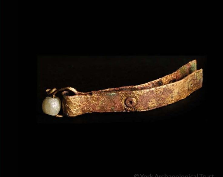 Viking age copper alloy tweezers stamped with ring-and-dot motifs, and a glass bead threaded onto the suspension ring that would have attached the tweezers to a belt or girdle. Found in York, UK.