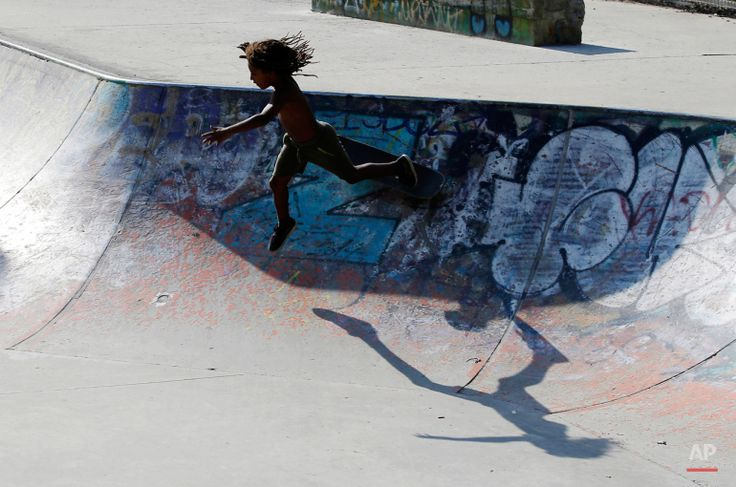 In this July 9, 2015 photo, a young skater falls as he plays in a skate park in Milan, Italy. (AP Photo/Antonio Calanni)