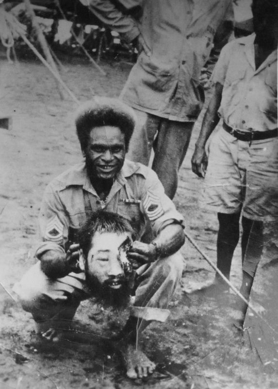 Master Sergeant US Army shows the severed head of a Japanese soldier in Okinawa