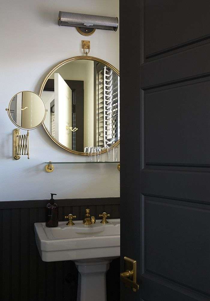 Rich gold hardware and ebony wainscoting evoke a fashionable moodiness in the bathroom of The Dean, a new 52-room hotel in Providence, Rhode Island.
