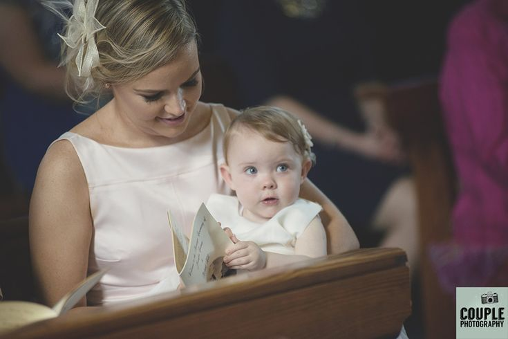 The flower girl tries to follow the ceremony. Weddings at Mullingar Park Hotel by Couple Photography.