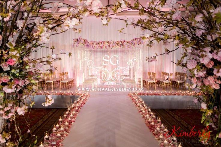 Suhaag Garden, Florida Indian wedding decorator, event design, event decor, Tampa Marriott Waterside Hotel & Marina, modern Mandap, stage, glass mandap, cherry blossom floral archway, wedding aisle, candles, petals