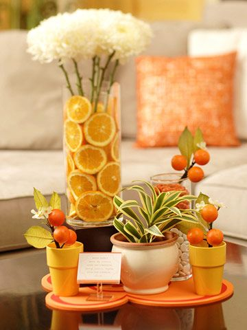 line a vase with lemon and orange slices. keep the slices in place by inserting a small vase inside the larger one, and drop the slices into the space between the vases. use the inside vase to hold flowers.