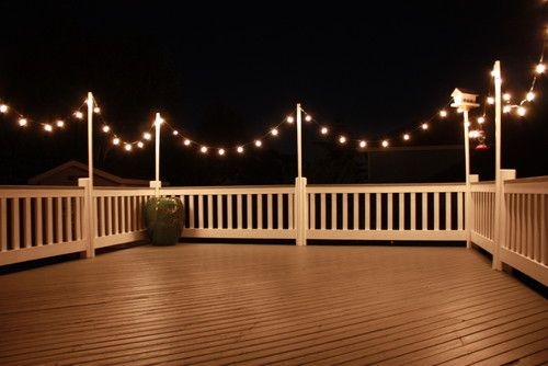 A string of lights swoops above the fence outlining this deck space. The string lights make this outdoor room feel like a party every night.