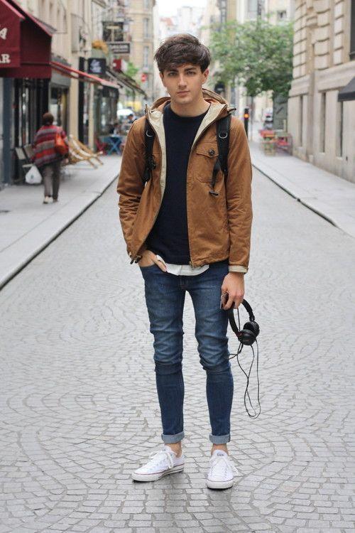blue rolled up jeans, a black sweater, an ocher jacket