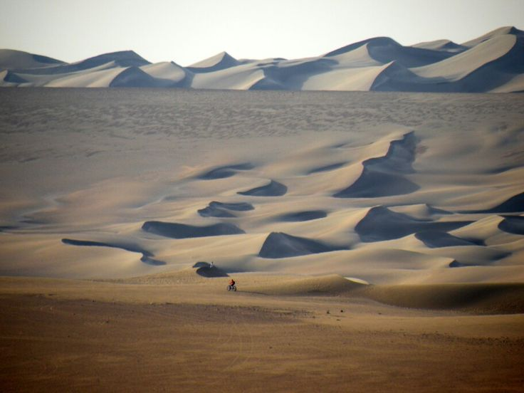 Seems just like a tiny point but it's another Fatbiker going down Atacama Desert sand dunes with us.