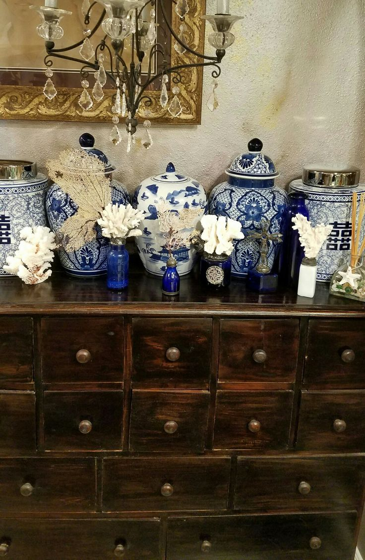 Blue and white ginger jars with coral vintage bottles.