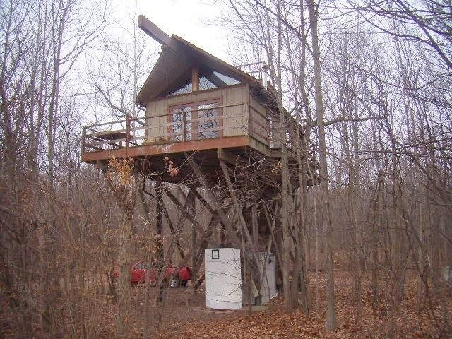 """Angola, IN - This treehouse with electricity, hot and cold running water and a wood-burning stove sits on nearly 44 acres in rural Indiana, alongside a 2-acre pond, a cottage that sleeps three and a large shed """"for all the toys you could possibly need,"""" the listing promises.  Size: 288 square feet"""