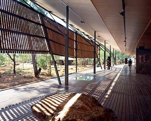 """Bowali Visitor Information Center  Kakadu National Park, Australia 1994  The team consulted members of the local Aboriginal population, leading to the use of regional materials, such as rammed earth, as well as larger curatorial strategies such as designing the museum to reflect the Aboriginal idea of """"a journey without beginning or end."""" The structure consists of a long butterfly roof and a large wooden brise-soleil that form a continuous verandah over a series of pavilions"""