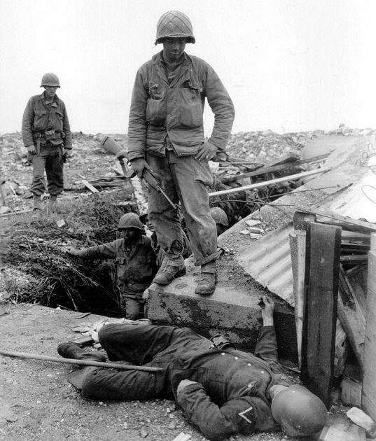 American soldiers standing right next to a dead soldier after the battle