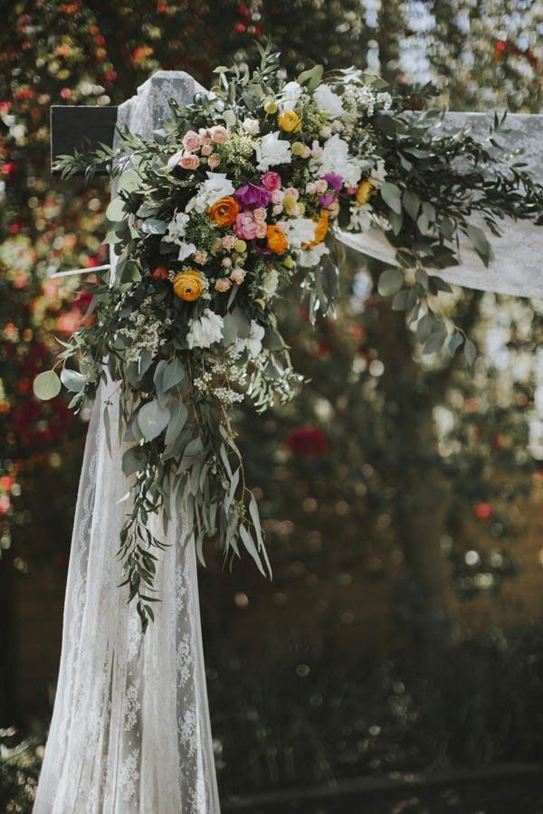 Wedding ceremony arch with lace drapery and a gorgeous floral arrangement   Image by Victoria Carlson Photography