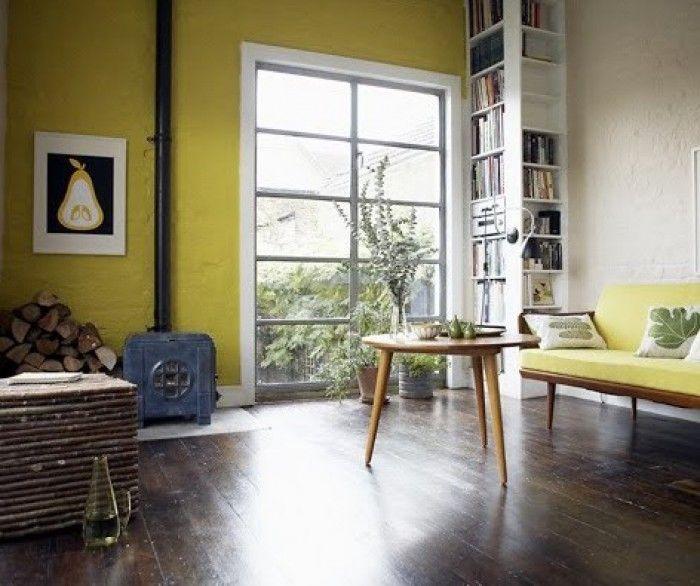Woonkamer met gele muur en donker houten vloer