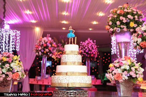 15 anos.Decoracao rosa e azul Tifany.bolo branco e dourados .laços e fitas douradas.Flores rosas, salmão, creme.laranja e pink.topo do bolo , boneca caricaturada da Debutante usando vestido azul Tifany da balada de sua festa