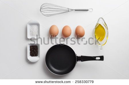 Scrambled eggs ingredients over white table, above view