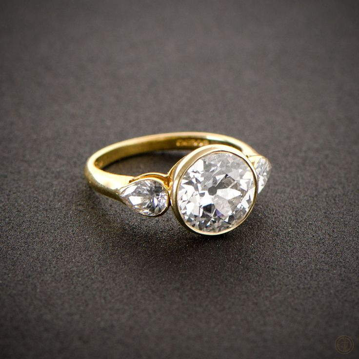 A stunning English Vintage Engagement Ring, bezel set in a beautiful yellow gold setting and shouldered by two pear-cut diamonds. Circa 1960.