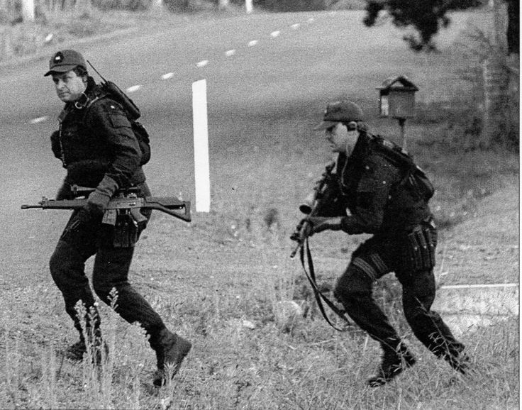 """Members of Tasmania Police Special Operations Group (SOG) race across the Tasman Highway to take up their positions outside the Seascape Guest House. (Photo: Robin Lane, from """"Suddenly One Sunday"""")"""