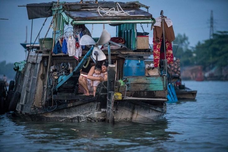 "DECEMBER 19, 2017HOME SWEET BOAT  A mother and child share a moment on their houseboat on the Mekong River in Can Tho, Vietnam. Can Tho is the largest city in the Mekong Delta, and at 105 miles from Ho Chi Minh City, is nicknamed ""the western capital.""  PHOTOGRAPH BY ANDY HOUSE,"