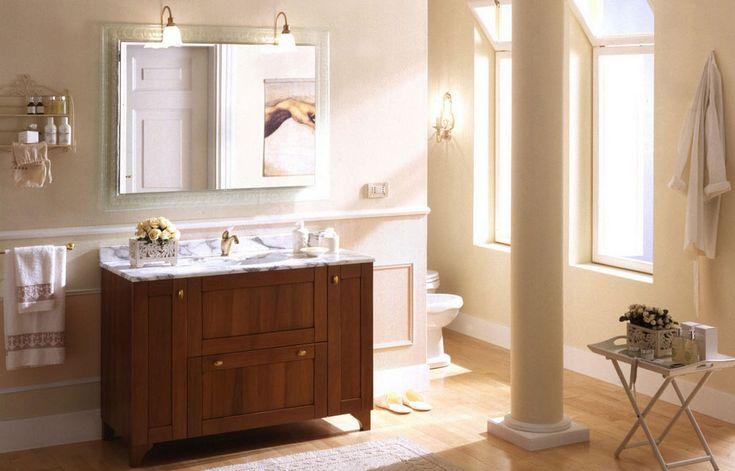 arredo bagno classico con due specchio e due lampade e tavolo in legno color marrone scuro e panna parete colorata evoca l'atmosfera classica in bagno | Arredamento e Decorazioni Per La Casa